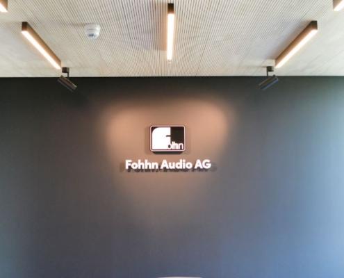 Silvoller Konferenzraum, dunkle wände, beleutetes Logo, Holzdecke, Lichtstrahler