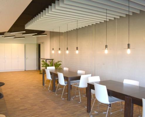 Tische mit Stühlen, Spints, tiefe Lampen, warmes Licht, Holz Boden, Schallschluckende Decken